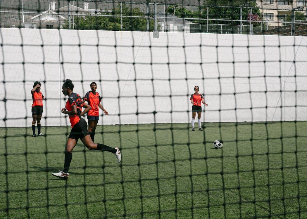 Girls Playing Soccer on Green Grass Field