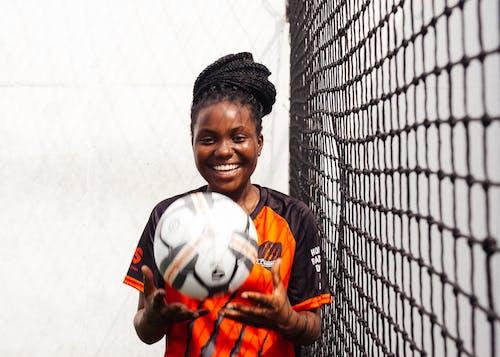 Smiling Girl in Black and Orange Uniform Holding Soccer Ball