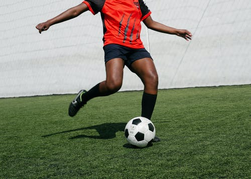 Person In Red Shirt And Black Shorts Playing Soccer