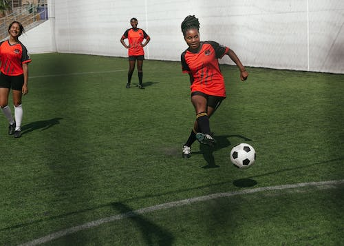 Woman In Red Soccer Jersey Playing Soccer On Green Field