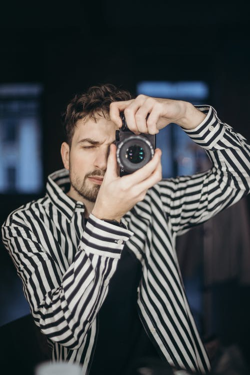 Man In Black And White Striped Long Sleeve Shirt Holding Black Camera