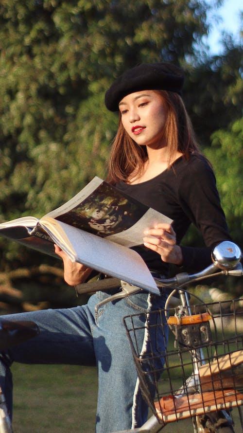 Immagine gratuita di berretto, bicicletta, donna, leggendo