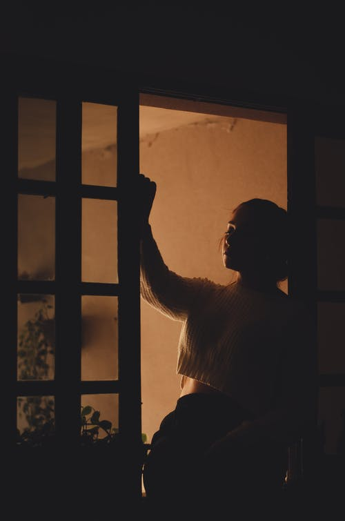 Silhouette of Woman Standing Near Window