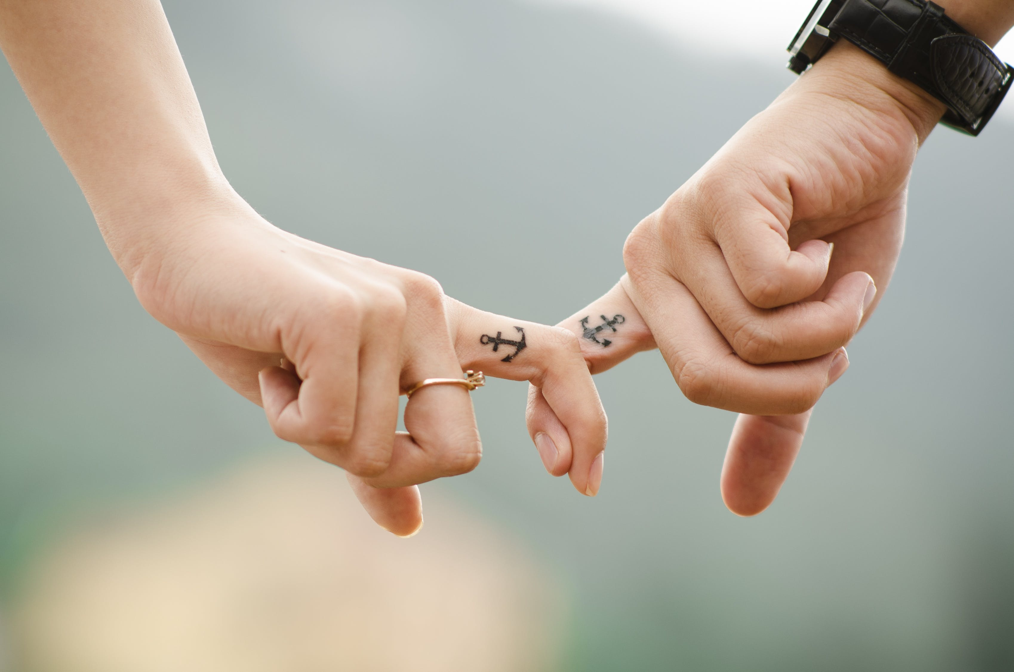 Married couple's pointed fingers are put together while their fingers are tattooed with anchor art