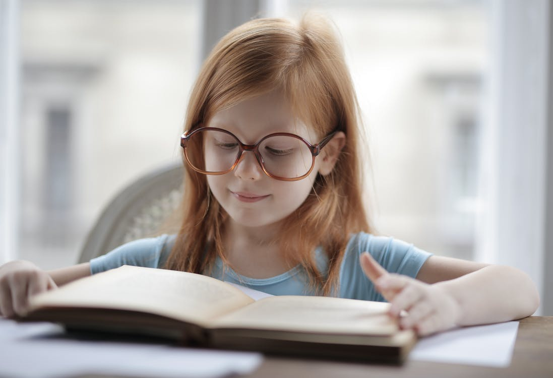 Girl In Blue Shirt Wearing Eyeglasses Reading A Book