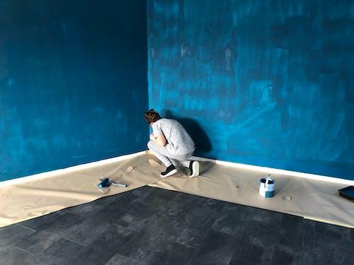 Woman In Gray Shirt And Gray Pants Painting The Walls