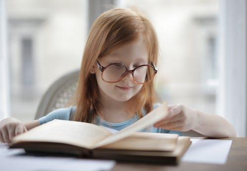 Girl Reading A Book With Eyeglasses