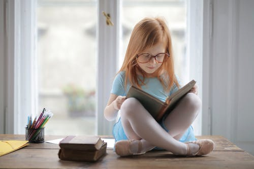 Girl In Blue Shirt Reading A Book