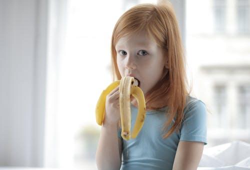 Girl In Blue Crew Neck T-shirt Holding Yellow Banana