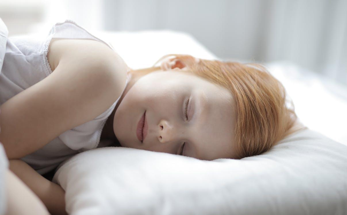 Happy cute girl sleeping in bed peacefully