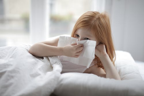Cute unhealthy child with red hair blowing nose with paper towel while lying on bed with white linen in cozy light bedroom