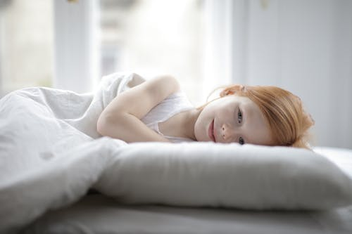 Girl Lying on White Bed