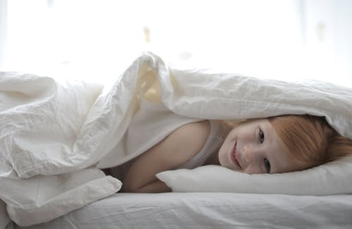 Girl Lying On Bed Covered With White Blanket