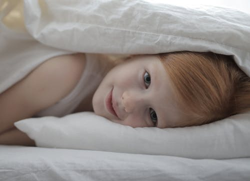 Peaceful cute girl lying in bed after awaking