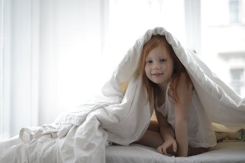 Girl With White Blanket On Her Head In Bed
