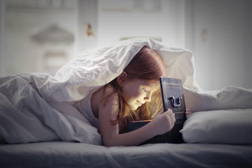 Girl Lying on Bed Looking At An Open Lighted Box