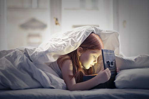 Girl on Bed Looking At An Open Lighted Box