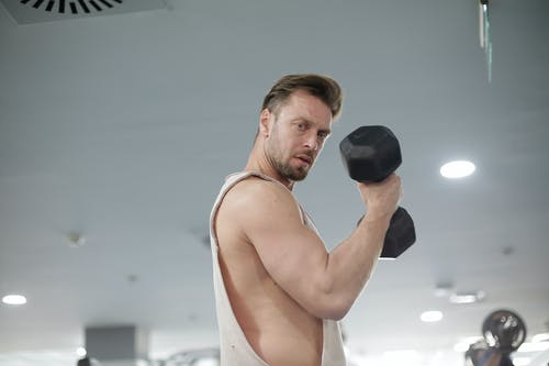 Man in White Tank Top Holding Black Dumbbell