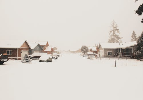 Brown and White Houses on Snow Covered Ground