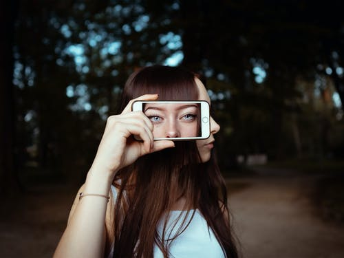 Woman Holding Smartphone With Background Of Woman's Face