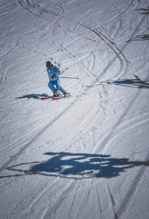 Person Riding on Ski Blades on Snow Covered Ground