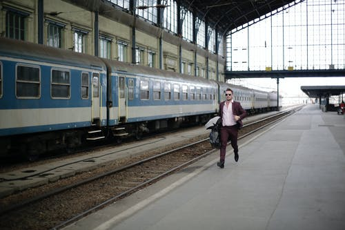 Man in a Purple Suit Running Beside Blue and White Train