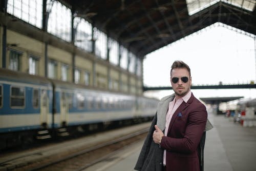 Confident adult businessman in formal suit on railway station