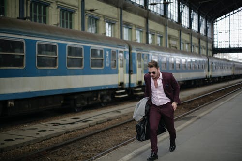 Man in Purple Suit Walking Beside Blue Train Carrying Luggage