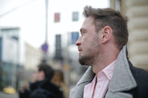 Stylish handsome man in warm outerwear on urban street