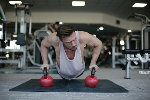 Strong sportsman during training with kettlebells in gym