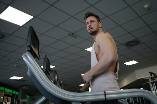 Strong sportsman using treadmill for cardio workout in gym