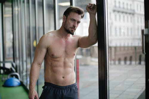 Adult brutal shirtless male athlete standing with raised hand on glass wall and looking away thoughtfully while resting between training in fitness club