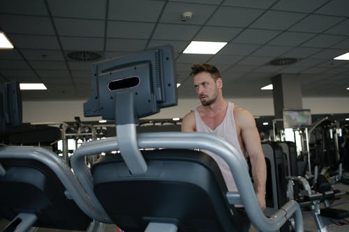 Powerful sportsman with closeup treadmill during cardio workout in gym