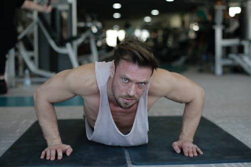 Focused sportsman doing push up exercise in gym