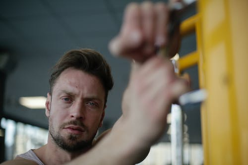 Confident strong adult sportsman in gym during workout