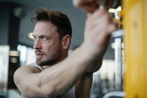 Confident strong adult sportsman during workout in gym