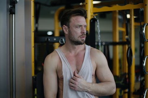 Strong muscular adult sportsman in gym during break in training