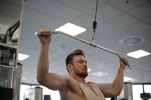 Man in White Tank Top Holding Exercise Equipment