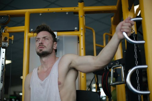 Man in White Tank Top Holding an Exercise Equipment