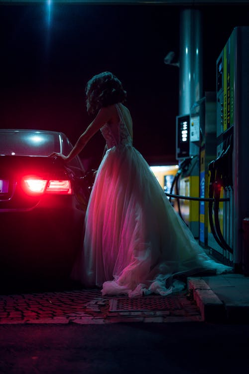 Woman in White Dress Fueling Car During Night