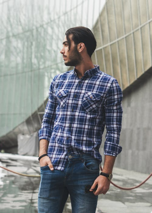 Man in Blue and White Plaid Shirt and Denim Jeans Standing on Concrete Ground