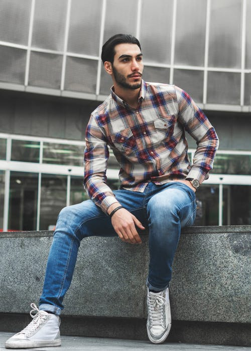 Man in Plaid Shirt and Blue Denim Jeans Sitting on Concrete