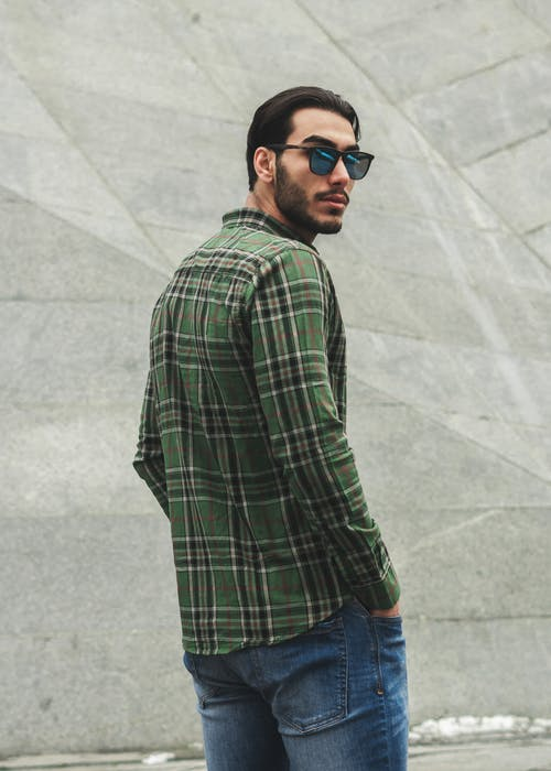 Man in Green and Black Plaid Shirt and Blue Denim Jeans Standing Near A Gray Concrete Wall