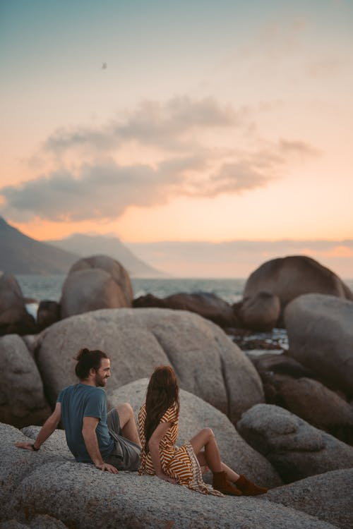 Man and Woman Sitting on Rock during Sunset