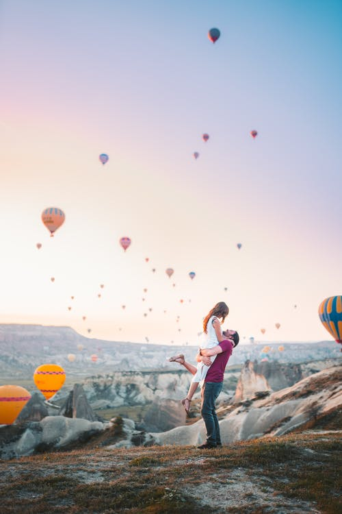 Man Carrying Woman With Hot Air Balloons Background