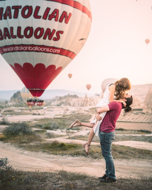 A Happy Couple With Hot Air Balloon On Background