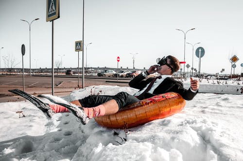Man Wearing A Suit Lying On Orange Inflatable Ring On A Snow