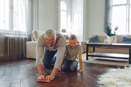 Man Wiping Brown Wooden Floor