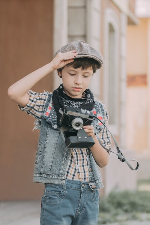 Boy in Blue Denim Jacket Holding Black and Gray Camera