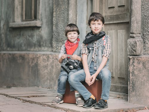 Photo Of Boys Sitting Near Doorway